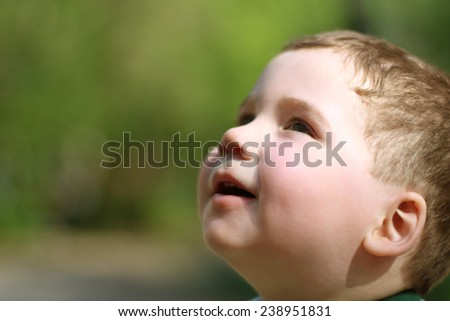 Smiling little cute boy looks up in park at summer day. Shallow dof - stock photo