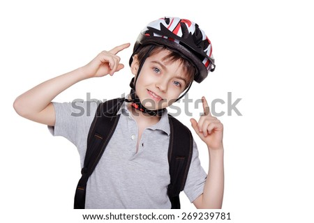smiling little cyclist pointing on his helmet - stock photo