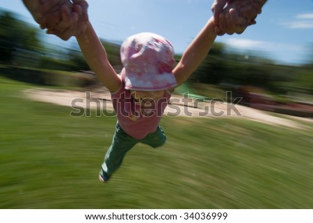 Smiling little girl airborne while rotating by holding the hands of her father, motion blur applied to accent speed - stock photo