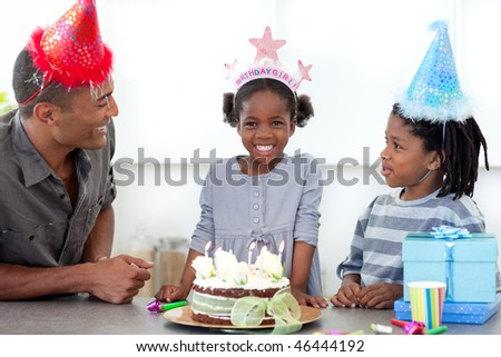 Smiling little girl and her family celebrating her birthday in the kitchen - stock photo