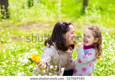Smiling little girl and her mother having fun at park early spring. Bright green grass and wild white flowers as a background. - stock photo