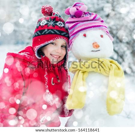 smiling little girl and snowman - stock photo