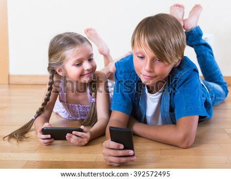 Smiling little girl and teenage boy burying in mobile phones laying on the floor