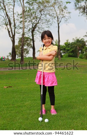 Smiling little girl at golf club - stock photo