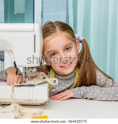 smiling little girl at the table with sewing machine looking at camera