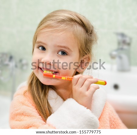 Smiling little girl brushing teeth in bath  - stock photo