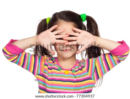 Smiling little girl covered his eyes with his hands and peep through fingers