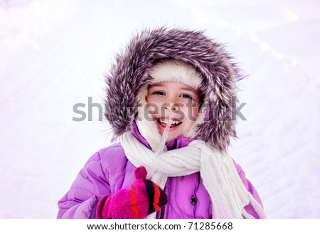 Smiling little girl dressed warmly holding an icilce outdoors
