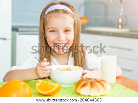 smiling little girl eating cereal with the milk - stock photo