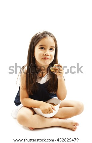 Smiling little girl eating cookie or biscuit, looking up. Isolated on white background - stock photo