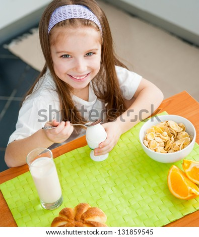 smiling little girl eating egg in the kitchen - stock photo