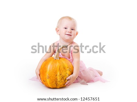 smiling little girl embraces pumpkin and a crystal shoe near by