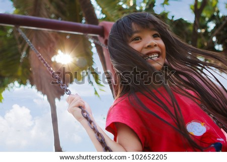 Smiling little girl enjoys playing in a children playground - stock photo