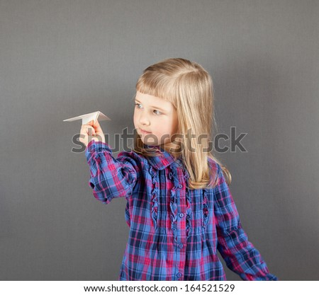 Smiling little girl flying paper plane on grey background