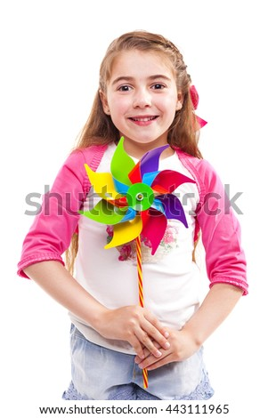 Smiling little girl holding a colorful toy windmill, isolated on white background - stock photo