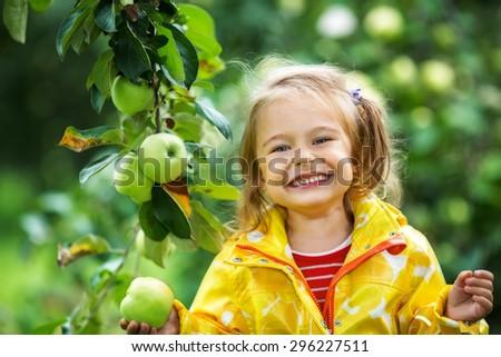 Smiling little girl holding apple in the garden - stock photo