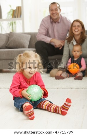 Smiling little girl holding ball at home with laughing family in background. - stock photo