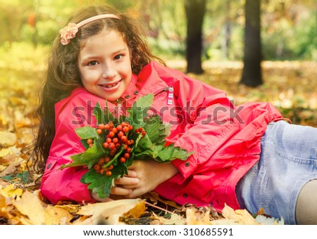 Smiling little  girl holding bouquet of ripe ashberries, sitting in a yellow sunny park - stock photo