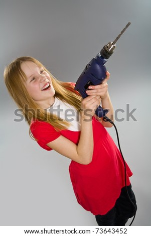 Smiling little girl holding electric drill - stock photo