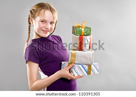 Smiling little girl holding gift boxes - stock photo