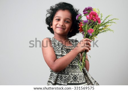 Smiling little girl holds a bunch of flowers - stock photo