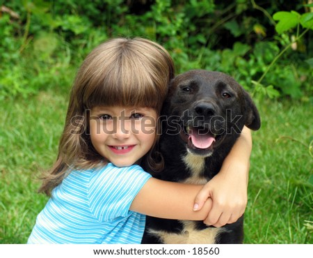 smiling little girl hugging a big black dog in an outdoor setting