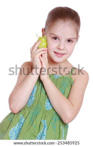 smiling little girl in a green dress is holding easter egg - stock photo