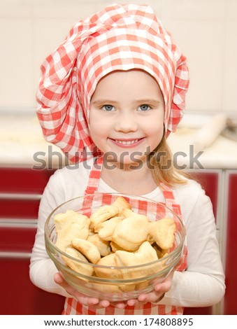 Smiling little girl in chef hat holding bowl with cookies in the kitchen - stock photo