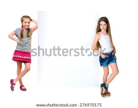 smiling little girl in full growth near the white banner - stock photo