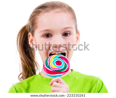 Smiling little girl in green t-shirt eating colored candy - isolated on white. - stock photo