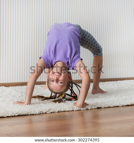 smiling little girl in lilac t-short engaged in fitness - stock photo