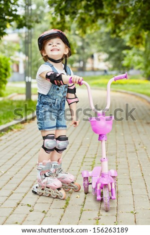 Smiling little girl in roller and protective equipment stands on walkway in park holding three-wheeled scooter - stock photo