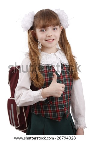 Smiling little girl in school uniform. Young pupil is going to school. School girl showing thumbs up on white background.  School girl is giving an ok gesture with her forward hand. Girl shows OK. - stock photo