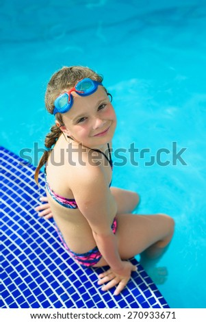 Smiling little girl in swimming goggles in the swimming pool