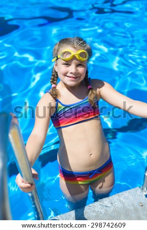 Smiling little girl in swimming goggles in the swimming pool - stock photo