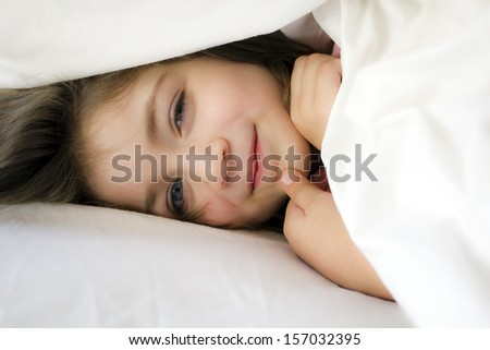 Smiling little girl in the bed under cover - stock photo
