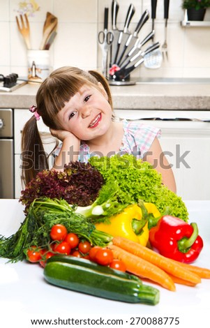 smiling little girl in the kitchen - stock photo