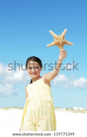Smiling little girl in yellow dress holding starfish - stock photo
