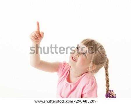 Smiling little girl indicating something, white background - stock photo