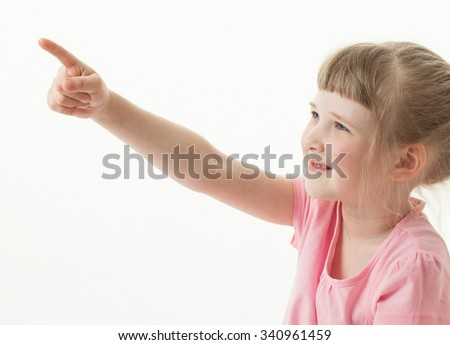 Smiling little girl indicating something, white background