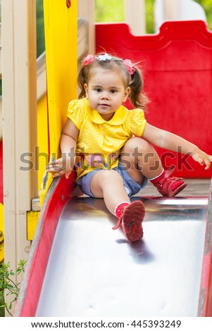 smiling little girl is sitting on a children's slide. She has fun on carousel
