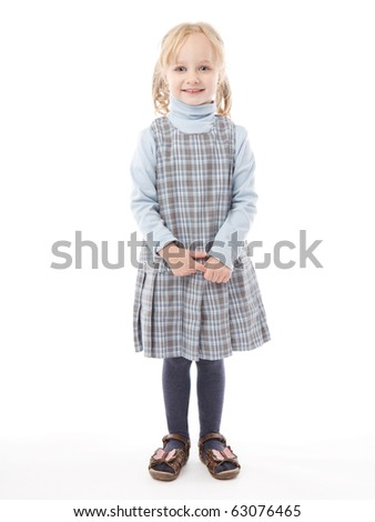 Smiling little girl is standing over white background - stock photo