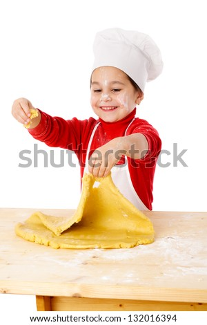 Smiling little girl kneading the dough for the cookies, isolated on white