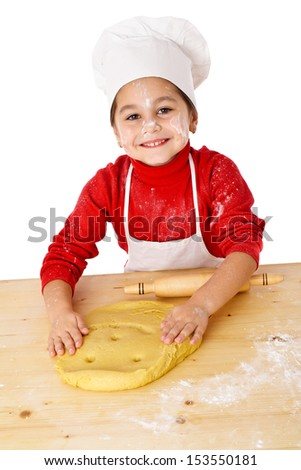Smiling little girl kneading the dough, isolated on white - stock photo