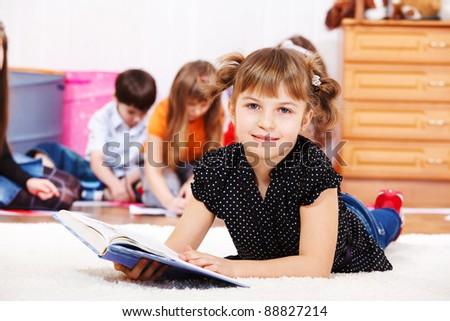 Smiling little girl lies on the floor with a book - stock photo