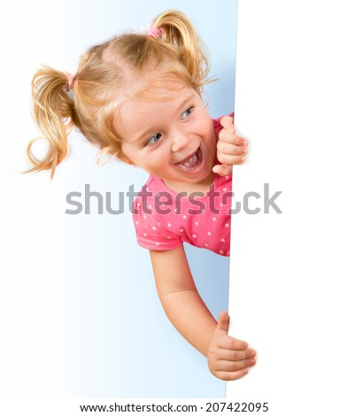 Smiling little girl looking behind a white board  - stock photo