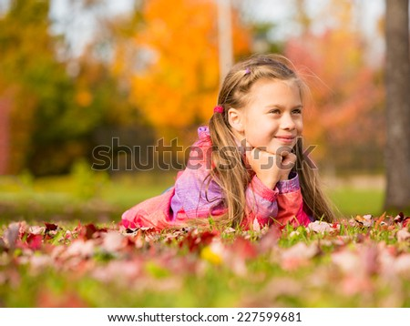 Smiling little girl lying on a colorful leaves in autumn park - stock photo