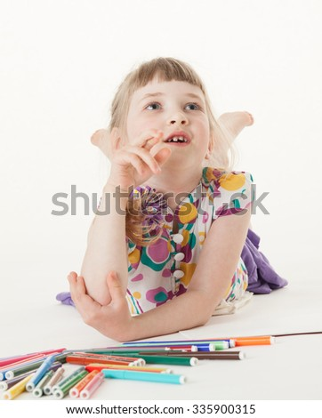 Smiling little girl lying on the floor and thinking, white background - stock photo