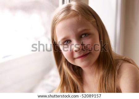 smiling little girl near window - stock photo