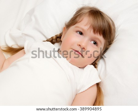 Smiling little girl on a bed